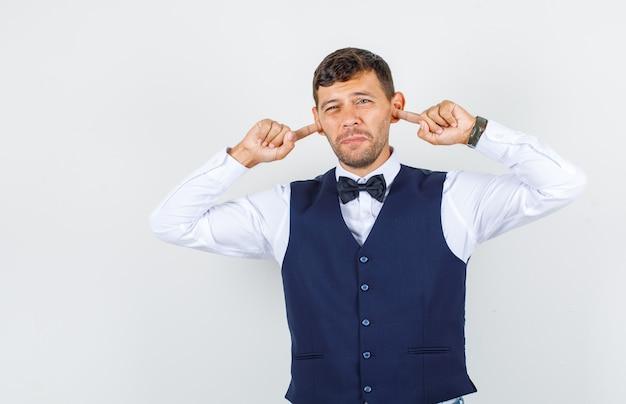 Официант затыкает уши пальцами в рубашку, жилет и выглядит раздраженным. передний план.