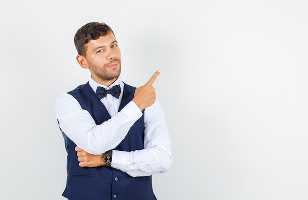 Waiter pointing away and smiling in shirt, vest and looking confident. front view.