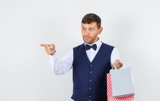 Waiter pointing away with paper bags in shirt, vest , front view.