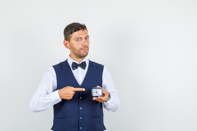 Waiter pointing at clock in shirt, vest and looking confident , front view.