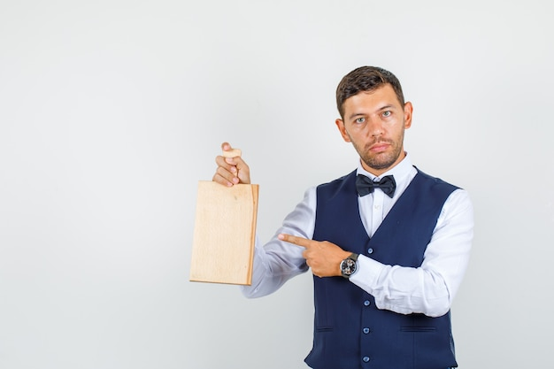 Waiter pointing at cutting board in shirt, vest and looking serious. front view.