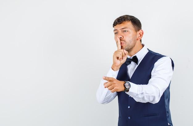 Cameriere che punta il dito via con gesto di silenzio in camicia, gilet e guardando attento, vista frontale.