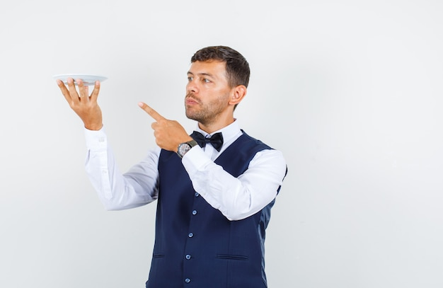 Waiter pointing finger at empty plate in shirt, vest and looking serious , front view.