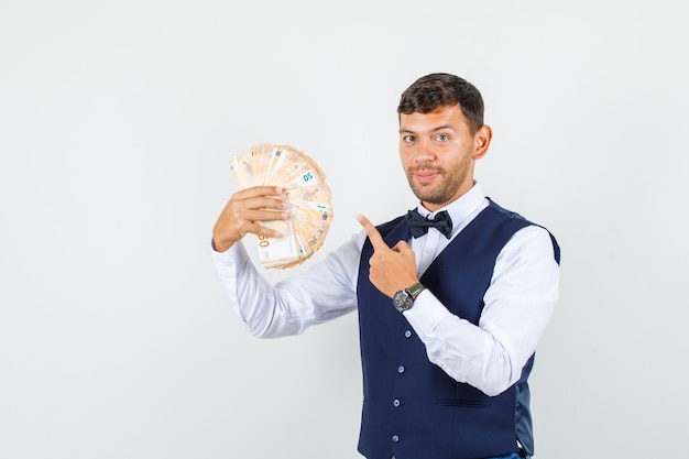 Waiter pointing finger at euro banknotes in shirt, vest and looking cheerful. front view.