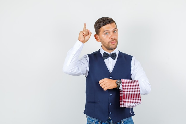 Waiter pointing finger up in shirt, vest, jeans and looking serious , front view.