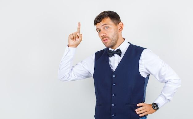 Официант показывает пальцем вверх с рукой на талии в рубашке, жилете и выглядит уверенно, вид спереди.