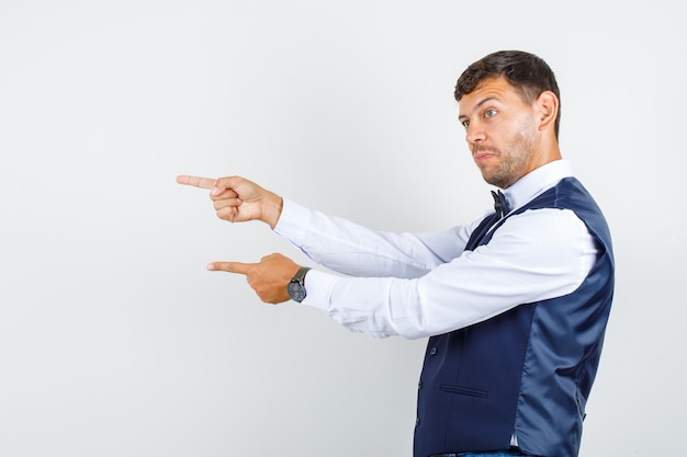 Waiter pointing fingers to side in shirt, vest and looking motivated. .