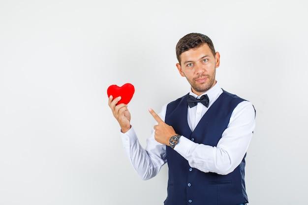 Cameriere che punta al cuore rosso in camicia, gilet e sembra fiducioso. vista frontale.
