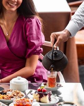 Cameriere che versa il tè nero in un bicchiere a forma di pera per la donna