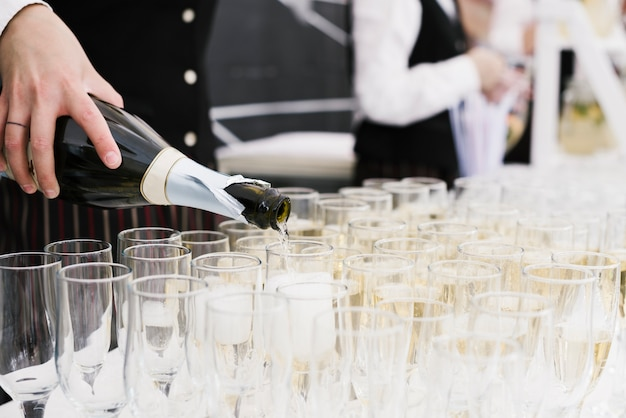 Waiter pouring champagne into glasses