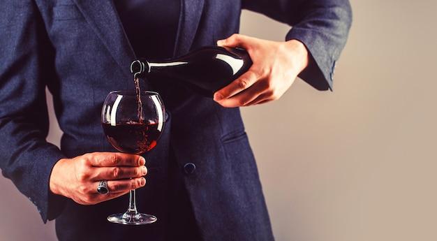 Официант наливает красное вино в бокал. мужчина-сомелье, дегустация, винодельня, мужчина-винодел. красное вино переливается из бутылки в бокал.