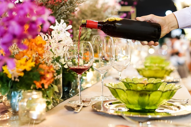 Waiter pouring wine into glass at luxury wedding