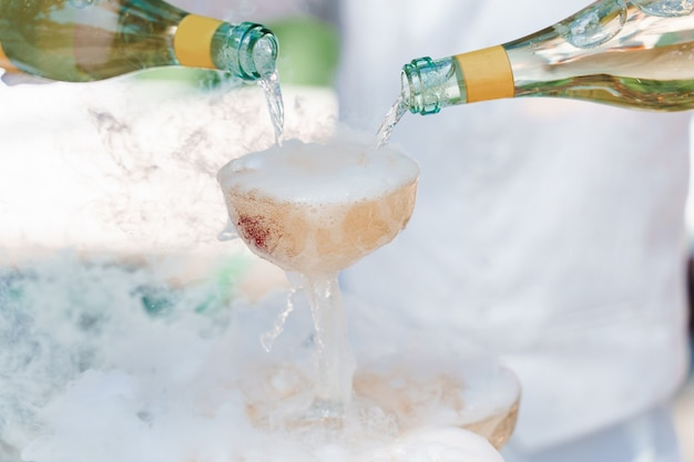 The waiter pours champagne from 2 bottles into crystal glasses with dry ice and white smoke close up