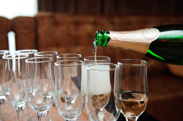 Waiter pours champagne in glasses, luxury event.