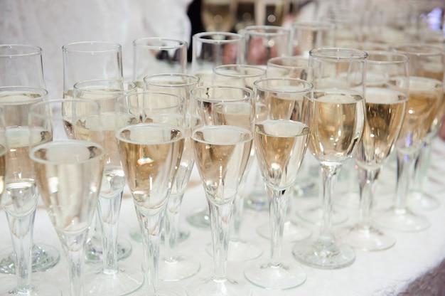 テーブルの上のグラスにシャンパンを注ぐウェイター