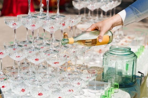 The waiter pours champagne into crystal glasses close up