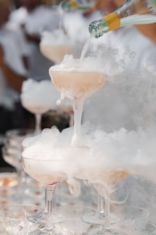The waiter pours champagne into crystal glasses with dry ice and white smoke close up