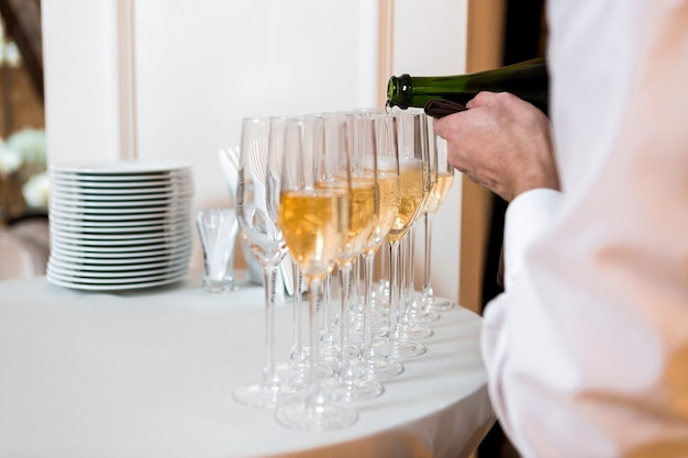 Waiter pours champagne. row of glasses at the celebration