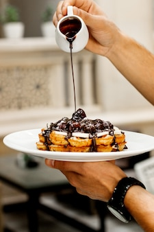 Waiter pours chocolate sauce on waffle with fruits