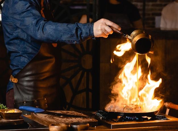 ウェイターはフライパンで燃えているステーキに油を注ぐ