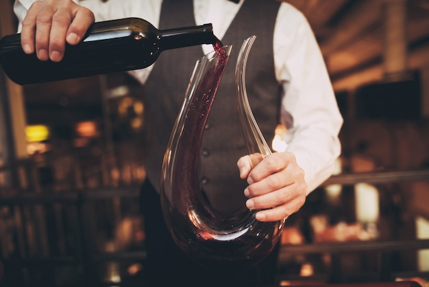 Waiter pours red wine from bottle into decanter.