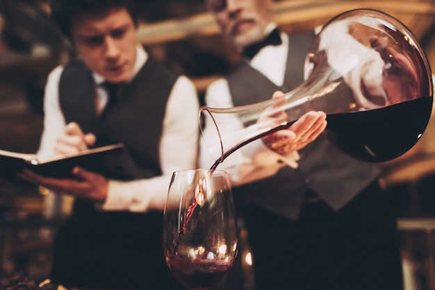 Waiter pours wine from decanter into glass.