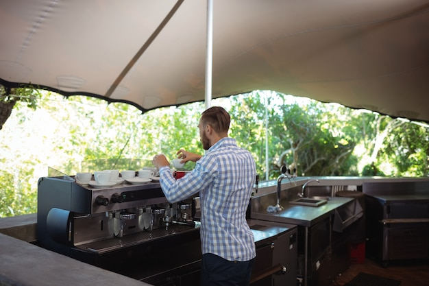屋外のカフェでコーヒーを準備するウェイター