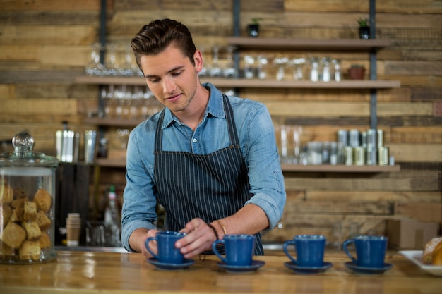 Waiter preparing cup of coffee at counter