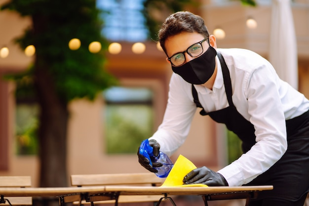 Waiter in protective mask and gloves disinfecting restaurant table for next customer.