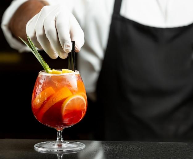 Il cameriere mette le cannucce di plastica nel cocktail di sangria in vetro