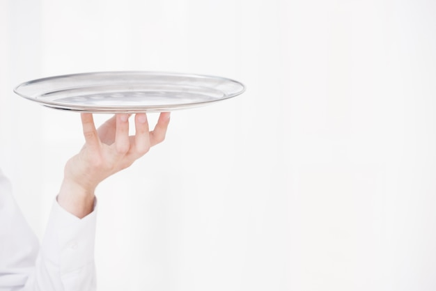 Waiter raising hand with metal tray
