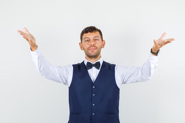 Cameriere che alza i palmi aperti come tenere qualcosa in camicia, gilet. vista frontale.
