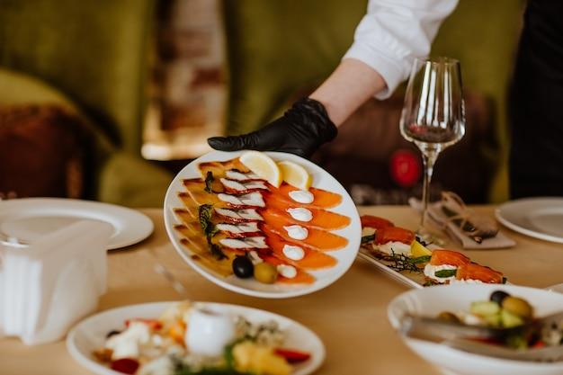 Рука официанта в черной медицинской перчатке держит тарелку с нарезкой копченой рыбы.