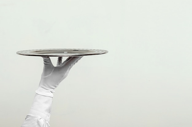 The waiter's hand in white gloves holds a silver tray.