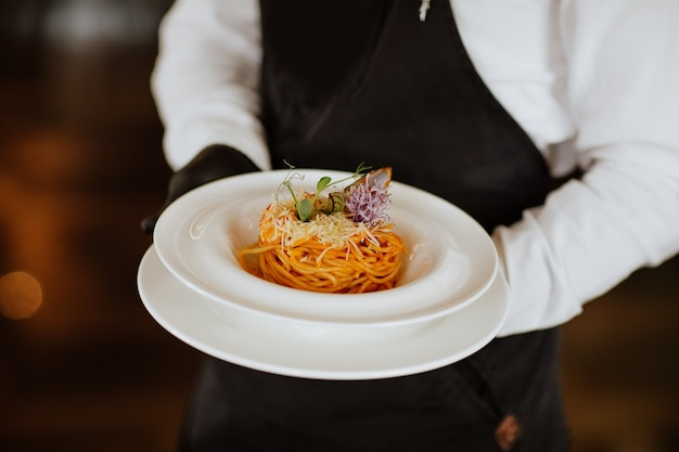 Руки официанта, держа свежие спагетти с морепродуктами на белой тарелке в ресторане.