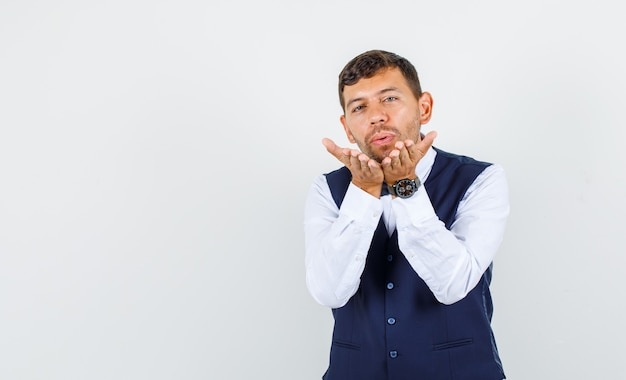 Waiter sending kiss by blowing on palms in shirt, vest and looking cute , front view.