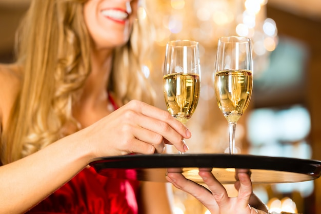 Waiter served champagne glasses on a tray in a fine dining restaurant and woman takes a glass, a large chandelier is in