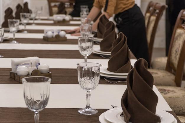 웨이터는 고급 레스토랑에서 연회 테이블을 제공합니다.
