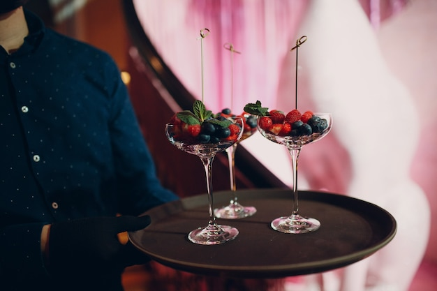 Waiter serves a dish in a restaurant with glass berries.