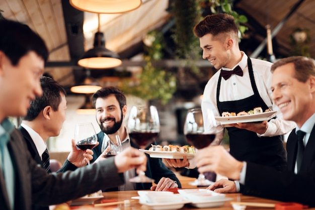 Waiter serves drinks and food for chinese business