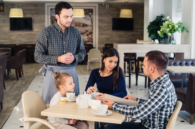 レストランで家族にサービスを提供するウェイター