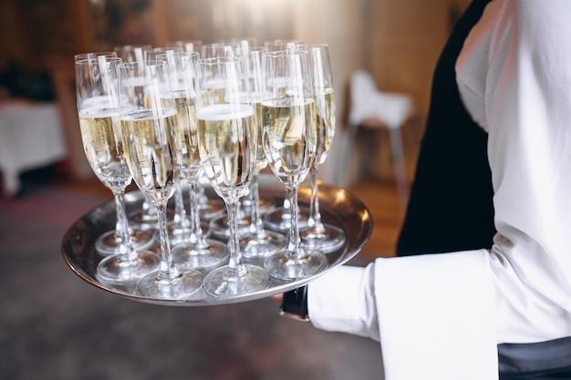 Официант подает напиток на подносе в ресторане