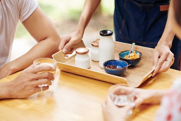 若いカップルのための朝食を提供するウェイター