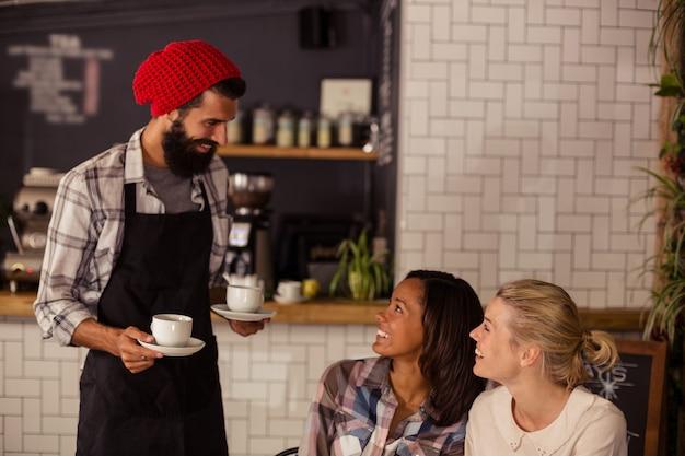 コーヒーを提供し、顧客とやり取りするウェイター