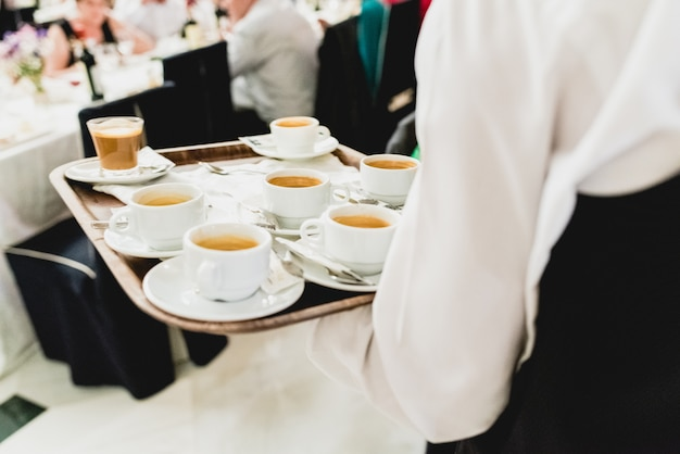 Waiter serving coffee during an event in cups.