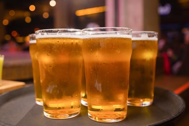 Официант, подающий бокалы холодного пива на подносе