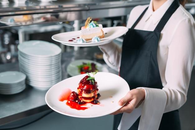 レストランで勤務中のウェイター。ウェイターは皿を運ぶ