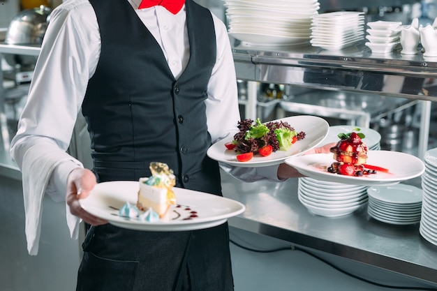 Waiter serving in motion on duty in restaurant. the waiter carries dishes