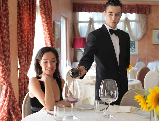 Waiter serving a pretty woman in a restaurant