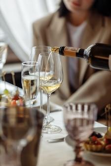 웨이터는 행복한 여성 고객이 테이블에 앉아 있는 고급 식당에서 레드 와인을 제공합니다.